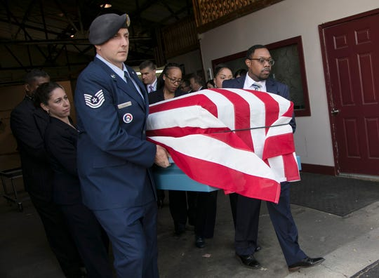 Technical Sgt. Patrick Probyn, Superintendent of Selfridge Air Force Base honor guard, helps to carry a coffin with veterans remains to a Verheyden Funeral Homes hearse in Flint Thursday, Oct. 25, 2018.