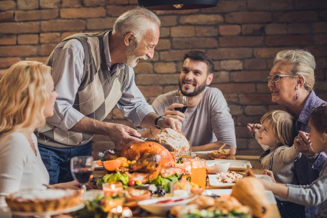 Extended family talking on Thanksgiving dinner at dining table