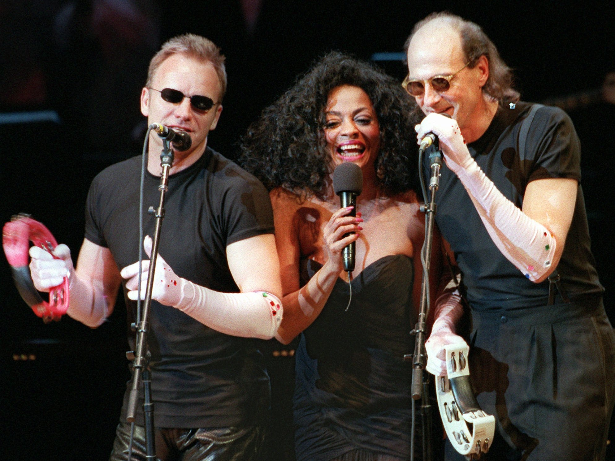 "Sting, left, and James Taylor, wearing Supremes-like long gloves, join Diana Ross on stage in New York's Carnegie Hall for the Rainforest Foundation's 1996 Benefit Gala, April 12, 1996. In the '90s, Ross created three made-for-TV movies, including ""Out of Darkness,"" in which she she played a schizophrenic."