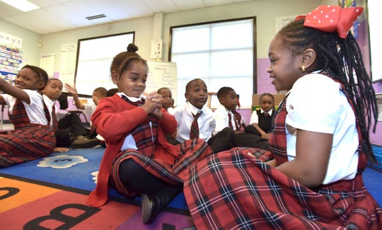 First-graders Bella Garcia, left, and Moria Jackson face each other during a reading exercise at Detroit Edison Public School Academy on Thursday morning.