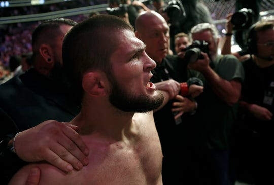 Khabib Nurmagomedov is held back outside of the cage after beating Conor McGregor at UFC 229 in Las Vegas.
