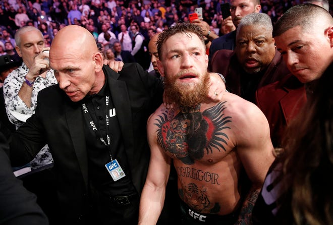 Conor McGregor is escorted from the cage area after fighting Khabib Nurmagomedov in a lightweight title mixed martial arts bout at UFC 229 in Las Vegas.