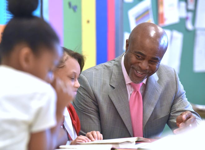 Ralph Bland, right, reads with fourth-graders, including, Sa'nay Pace, center, during class. Bland is the Detroit Edison Public School Academy CEO and president and founder of New Paradigm for Education.