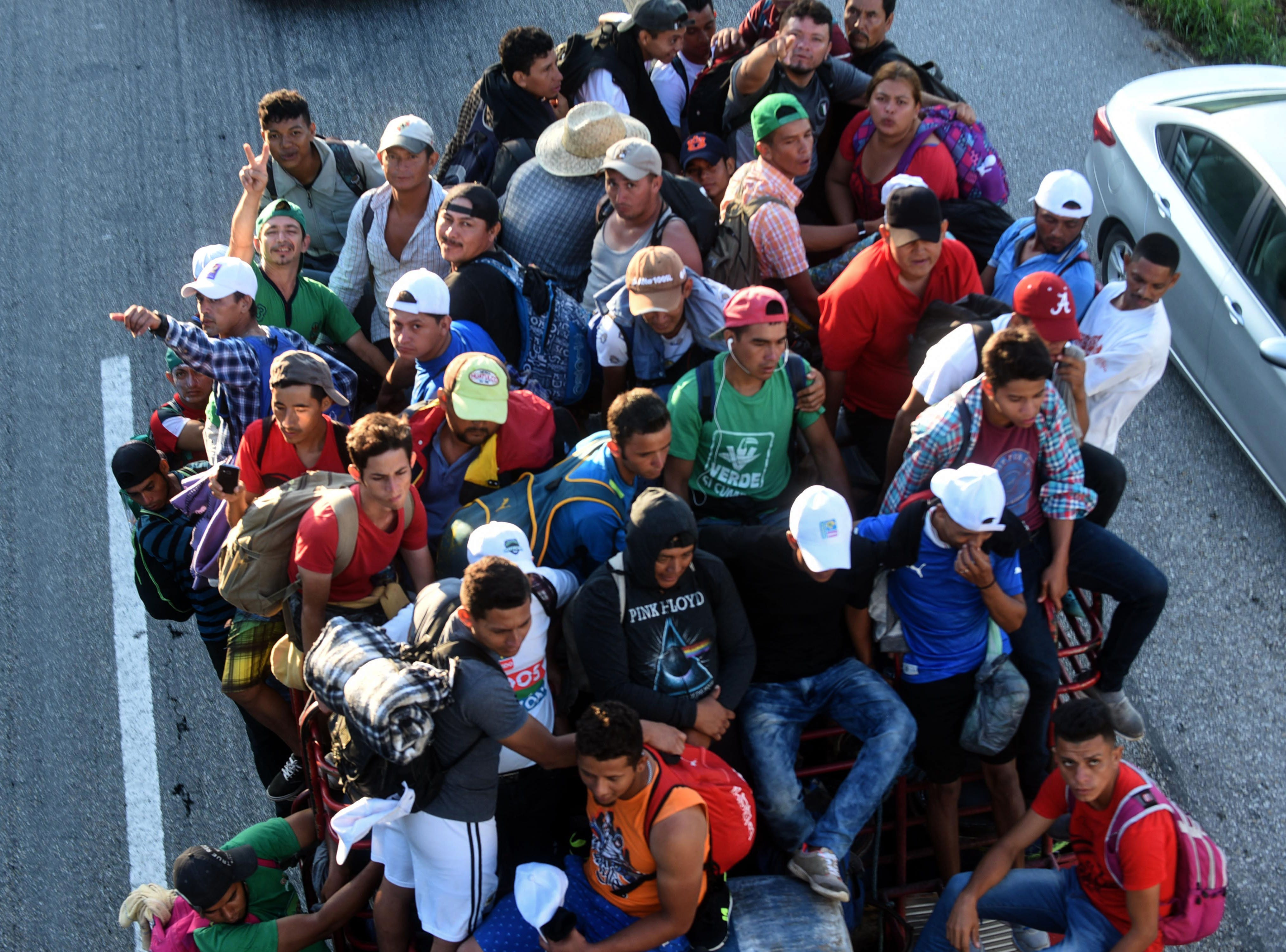 Honduran migrants heading in a caravan to the US, travel aboard a truck in Mapastepec on their way to Pijijiapan Chiapas state, Mexico, on October 25, 2018. - Thousands of Central American migrants crossing Mexico toward the United States in a caravan have resumed their long trek, walking about 12 hours to their next destination.