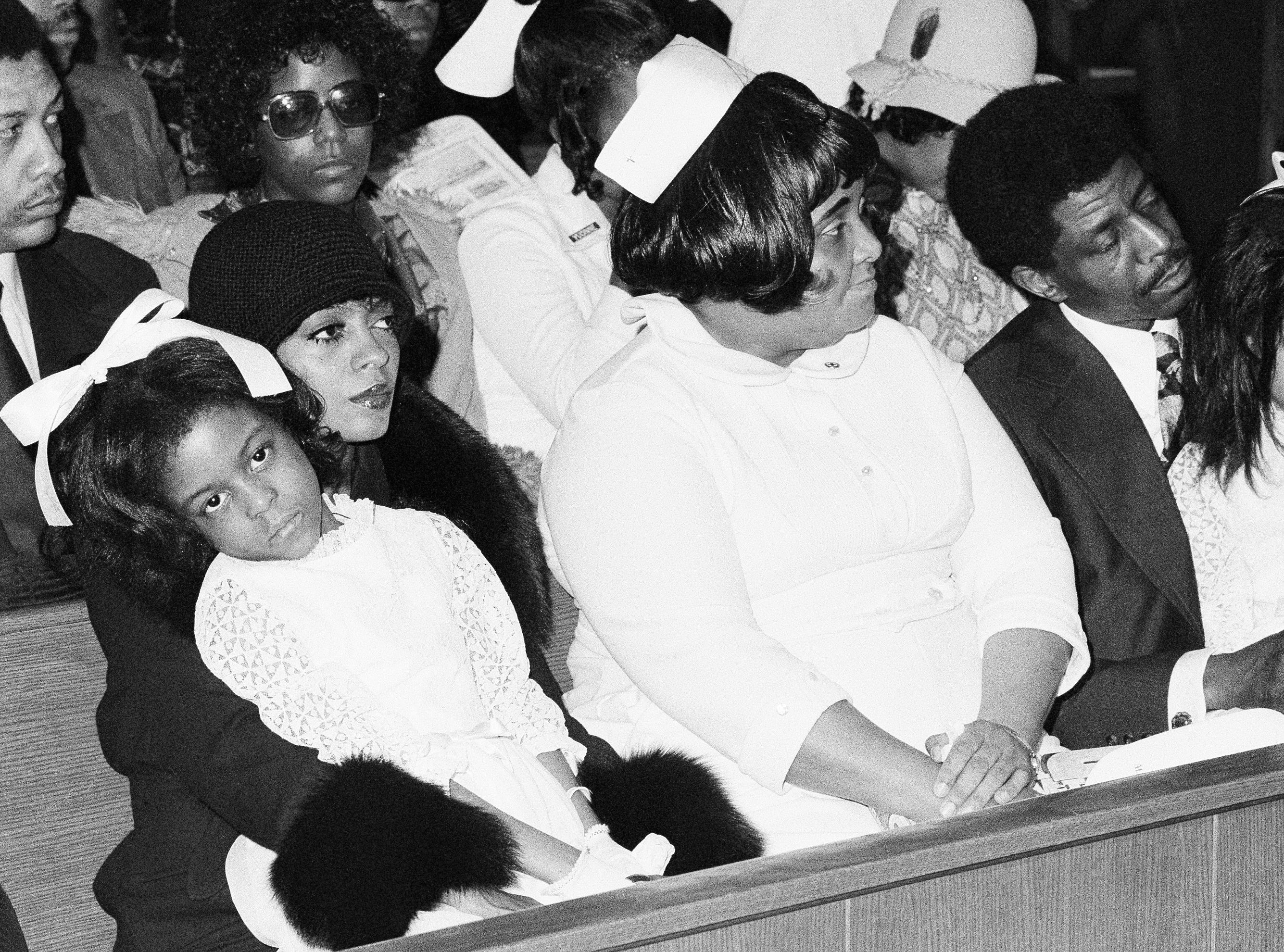 On Feb. 22, 1976, Florence Ballard died of a heart attack at the age of 32. During the funeral at Detroit's New Bethel Baptist Church, Diana Ross holds Lisa Chapman, 3, daughter of Florence Ballard. At far right is Ballard's husband, Tommy Chapman, and daughter Michelle Chapman, 7.