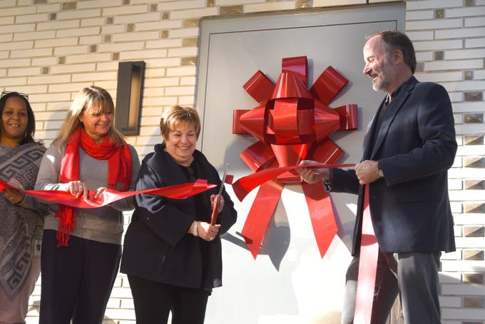 From left, Karl Williamson and Alison Watson watch Maxine Frankel cut the ribbon with Steve McBride, executive director of Pewabic Pottery, during a ceremony on Thursday October 25, 2018 for the Maxine and Stuart Frankel Pewabic Tile Studio. The  2,500 square-foot addition is the first expansion since 1912.
