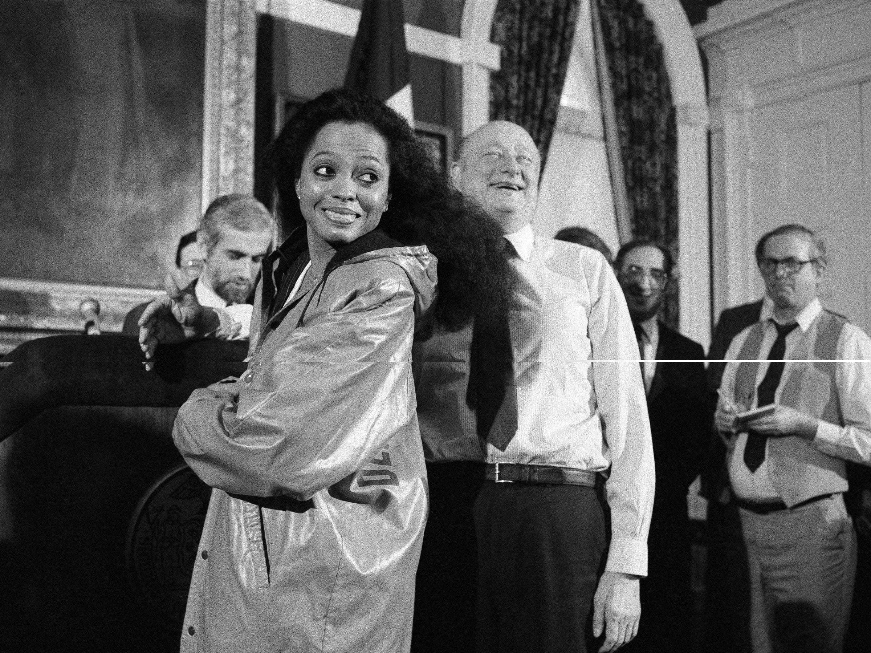 Diana Ross shows off her New York City Parks Department raincoat, Jan. 18, 1984 at City Hall. Mayor Edward Koch, right, presented the coat after Ross gave him a promised check for $250,000 for the construction of a children's playground in Central Park. The check was part of an agreement Ross made when she staged her free concert the previous summer in the park.