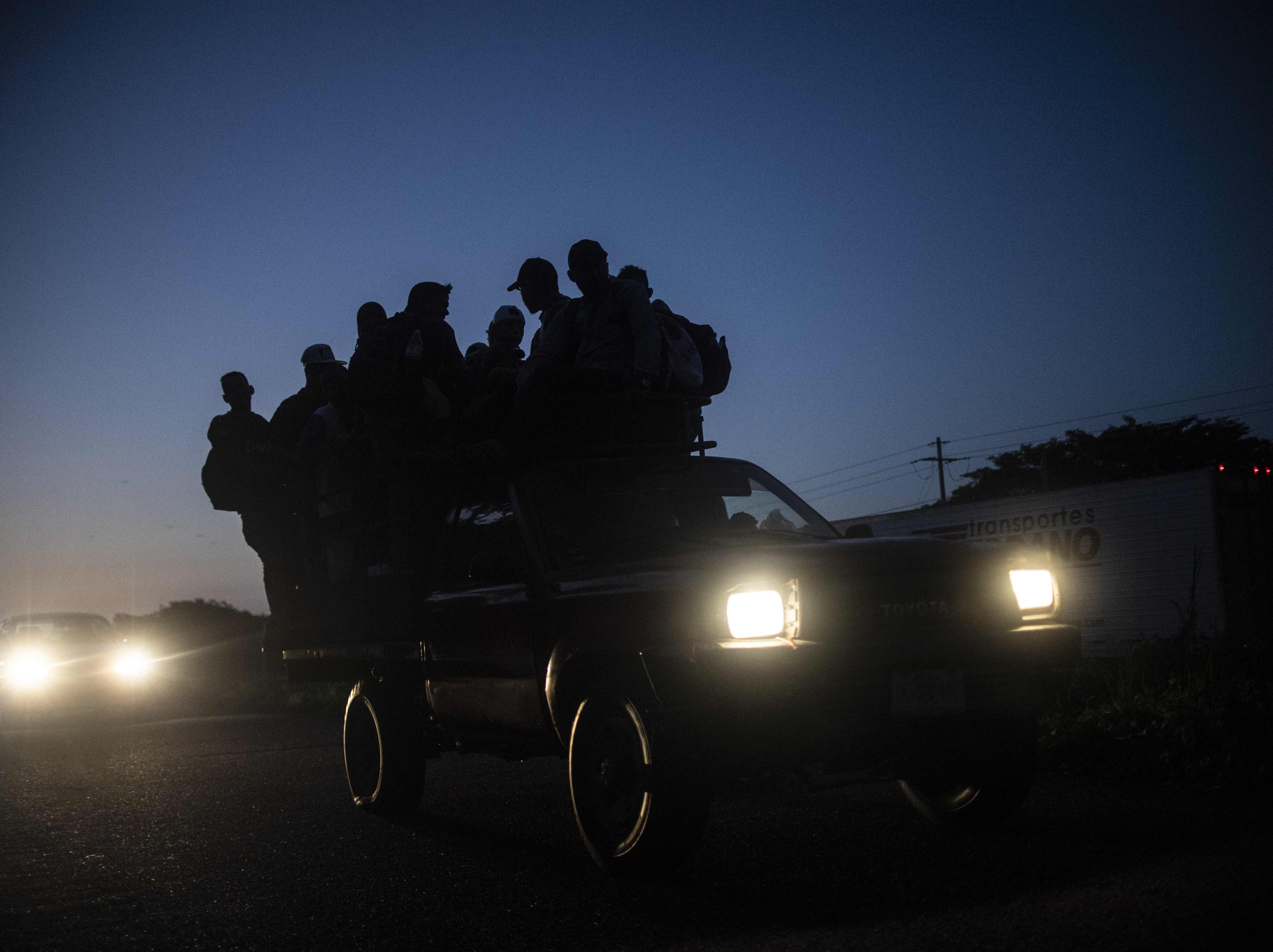 Honduran migrants heading in a caravan to the US, travel aboard a truck near Mapastepec, Chiapas state, Mexico, on October 25, 2018. - Thousands of Central American migrants crossing Mexico toward the United States in a caravan have resumed their long trek, walking about 12 hours to their next destination.