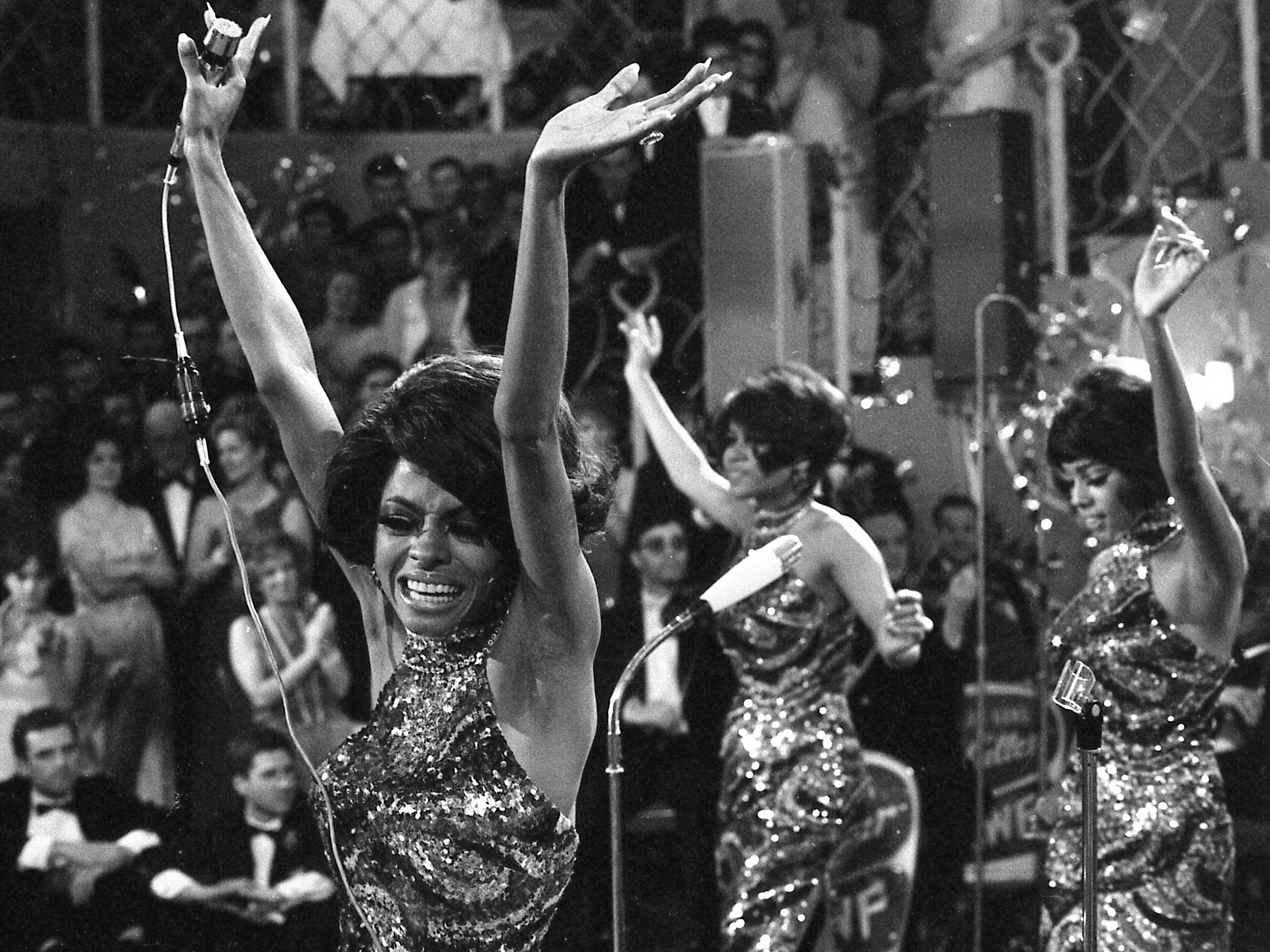 The Supremes with Diana Ross, front, Cindy Birdsong and Mary Wilson throw their arms in the air as they perform in Munich, West Germany, Jan. 21, 1968.