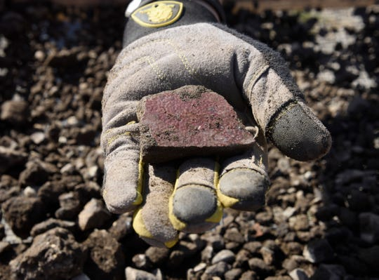Cory Taylor, 25, a Wayne State master's program student, displays a piece of pottery that she found while digging on the site where the Hamtramck fire station was located.