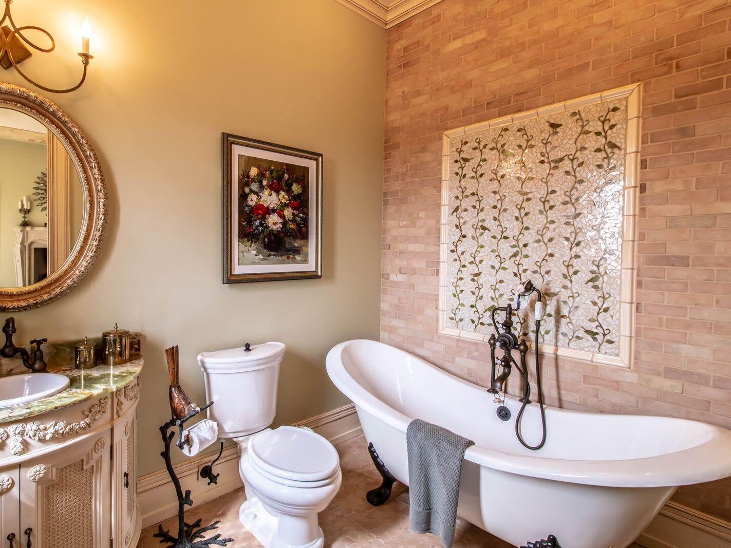 A stately bathroom with clawfoot tub.