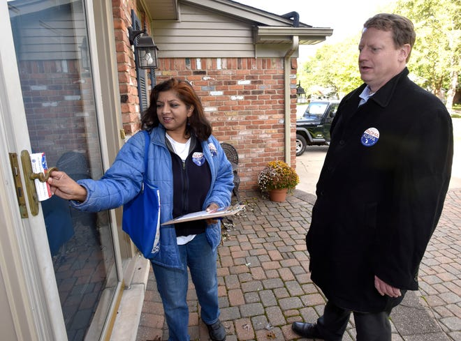 Padma Kuppa, a Democrat running for the 41st state House District that includes Troy and Clawson, puts a flyer in a door while campaigning in Troy with Tim Greimel, minority leader of the state House.