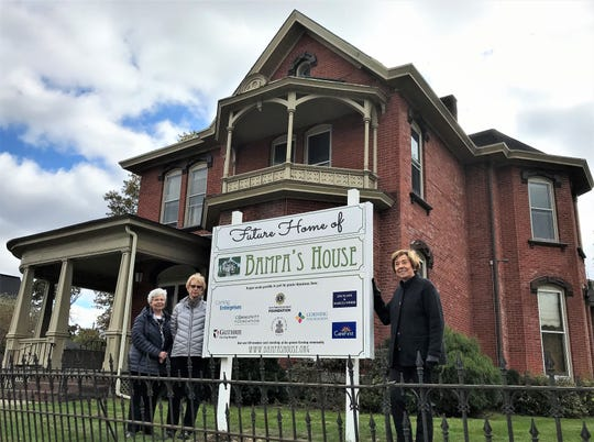Joan Wilson, right, president of the Bampa's House board, stands in front of the Corning comfort home's new location on East First Street, along with acting volunteer coordinator Rosemary Mullaney, left, and board Treasurer Charlotte Dugan.