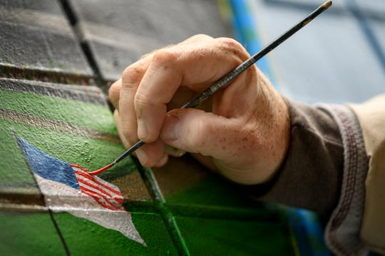 Michael Smith of Orange Moon Art Studio creates an American flag on the replica of historic Bosse Field inside the new Evansville mural located between Rumjahn Gallery and Innovation Pointe in downtown Evansville, Ind., Thursday morning, Oct. 25, 2018. The mural is expected to be completed in two weeks, weather permitting.