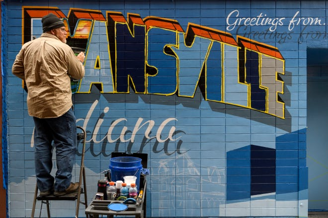 """Chandler artist Michael Smith of Orange Moon Art Studio creates a replica of historic Bosse Field inside the letter v on a new mural located between Rumjahn Gallery and Innovation Pointe in downtown Evansville, Ind., Thursday morning, Oct. 25, 2018. The Growth Alliance for Greater Evansville commissioned Smith and his wife, Amanda Smith, not pictured, to create the mural to transform the space into a """"self-E"""" alley for the community."""