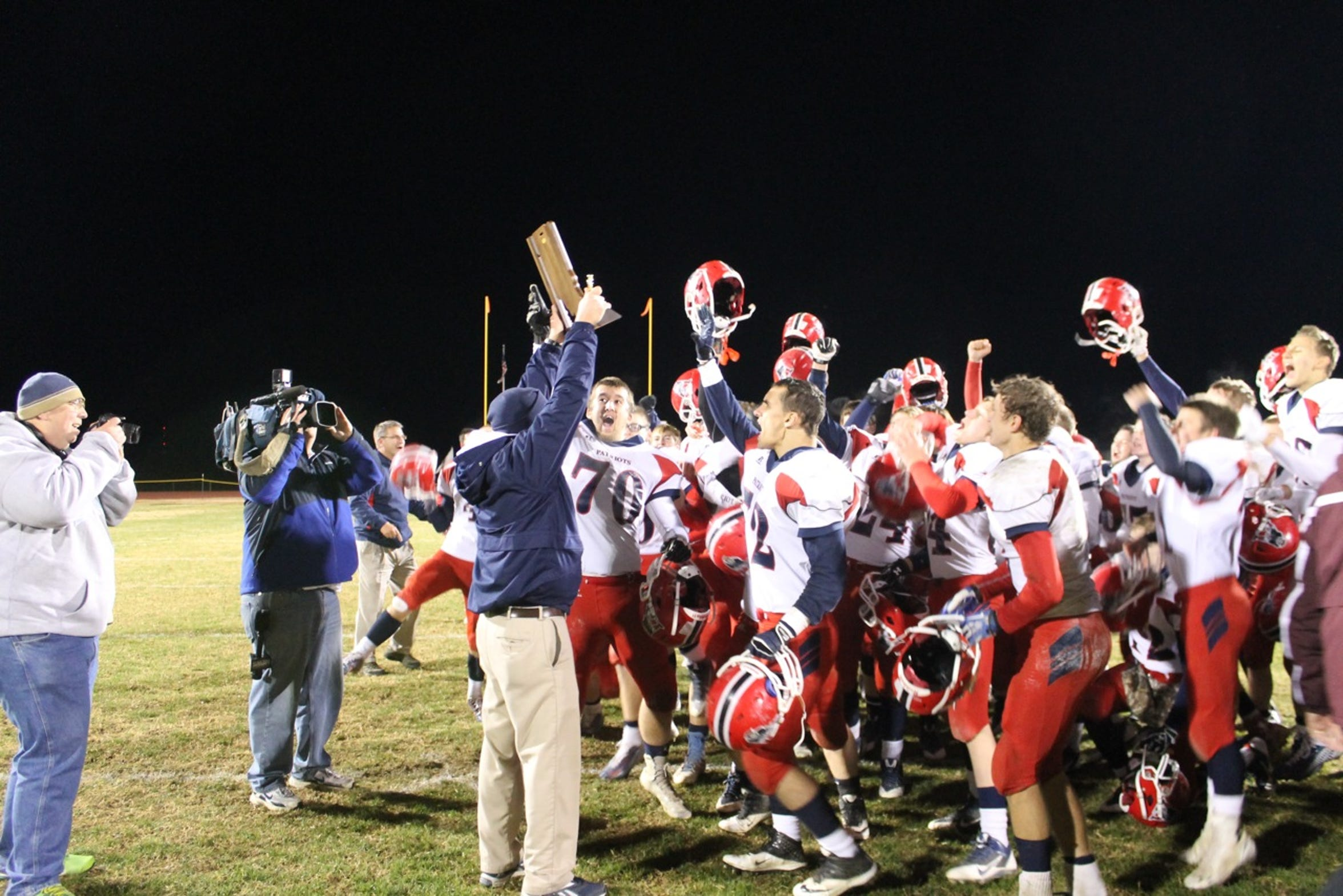 Heritage Hills football coach Todd Wilkerson hoists a sectional championship trophy after his team beat Gibson Southern, 14-13, on Nov. 7, 2014 in Fort Branch, Ind.