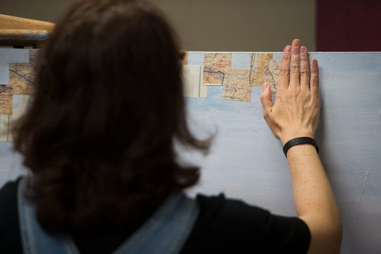 Fort Collins based artist Jennifer Davey pastes small squares of maps onto a one of her latest paintings on Tuesday, Oct. 23, 2018, at her studio in Loveland, Colo.