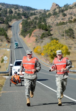 Two CSU Army ROTC cadets run the game ball that was given to them at the border on Oct. 24, 2014, by Army ROTC cadets from Wyoming at the state line along U.S. Highway 287 near Virginia Dale toward Fort Collins. This year's Bronze Boot Run begins at 7 a.m. Thursday in Laramie, Wyo., with a scheduled 5:30 p.m. arrival at CSU's Canvas Stadium. CSU is inviting fans to run alongside the cadets or line the streets to cheer them on for the final leg through campus from Moby Arena to the stadium.