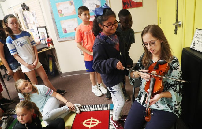 Kristen Long, a music teacher at Three Oaks Elementary School lets student, Asenet Carmona play a violin on Thursday 10/25/2018. The Music Foundation of Southwest Florida purchased three sets of new instruments that are being distributed throughout the school district. They bought the instruments with a $19,000.00 grant by the Suncoast Federal Credit union, the Gannett Foundation and Rotary International among other donations.