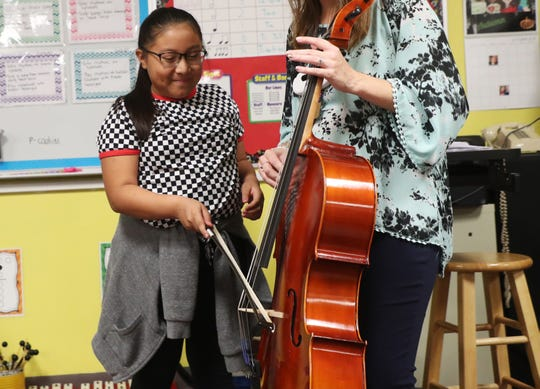 Three Oaks Elementary School fifth grader, Kayce Rodriguez,10, hears what a cello sounds like on Thursday 10/25/2018.  The Music Foundation of Southwest Florida purchased three sets of new instruments that are being distributed throughout the school district. They bought the instruments with a $19,000.00 grant by the Suncoast Federal Credit union, the Gannett Foundation and Rotary International among other donations.