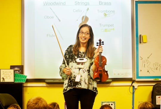 Kristen Long, a music teacher at Three Oaks Elementary School shows off a violin to her fifth grade students on Thursday 10/25/2018. The Music Foundation of Southwest Florida purchased three sets of new instruments that are being distributed throughout the school district. They bought the instruments with a $19,000.00 grant by the Suncoast Federal Credit union, the Gannett Foundation and Rotary International among other donations.