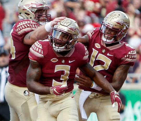 Florida State Seminoles running back Cam Akers (3) and Florida State Seminoles quarterback Deondre Francois (12) celebrate a touchdown against Wake Forest at Doak Campbell Stadium.