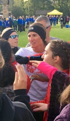 Pike coach Kendra Champion-McAloon addresses team in a pre-race huddle.