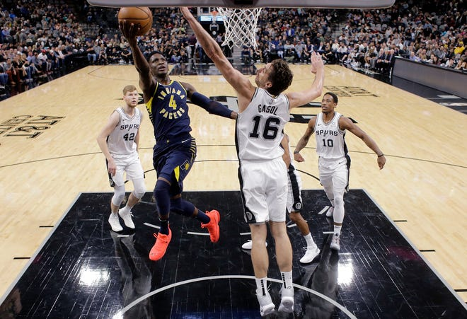 Indiana Pacers guard Victor Oladipo (4) scores past San Antonio Spurs center Pau Gasol (16) during the first half of an NBA basketball game, Wednesday, Oct. 24, 2018, in San Antonio.