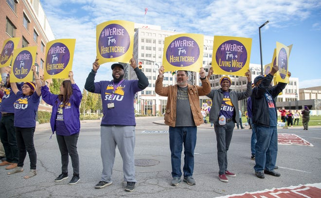 Jerome Perkins I (third from left) and City-County Councilor Zach Adamson (standing next to him) and others and others wait to be issued summonses during a protest in front of Eli Lilly and Co. headquarters, Indianapolis, Thursday, Oct. 25, 2018. SEIU Local 1 and supporters blocked traffic in front of Eli Lilly headquarters.