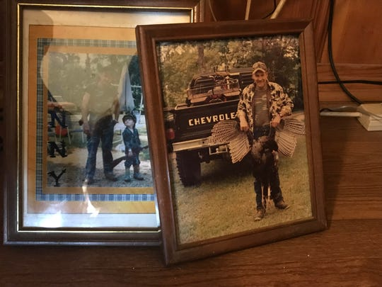 The McCombs family has photographs of Danny McCombs, who is believed to have been found Saturday, scattered around their living room in preparation for his memorial service. He is shown here holding a turkey he killed while hunting.