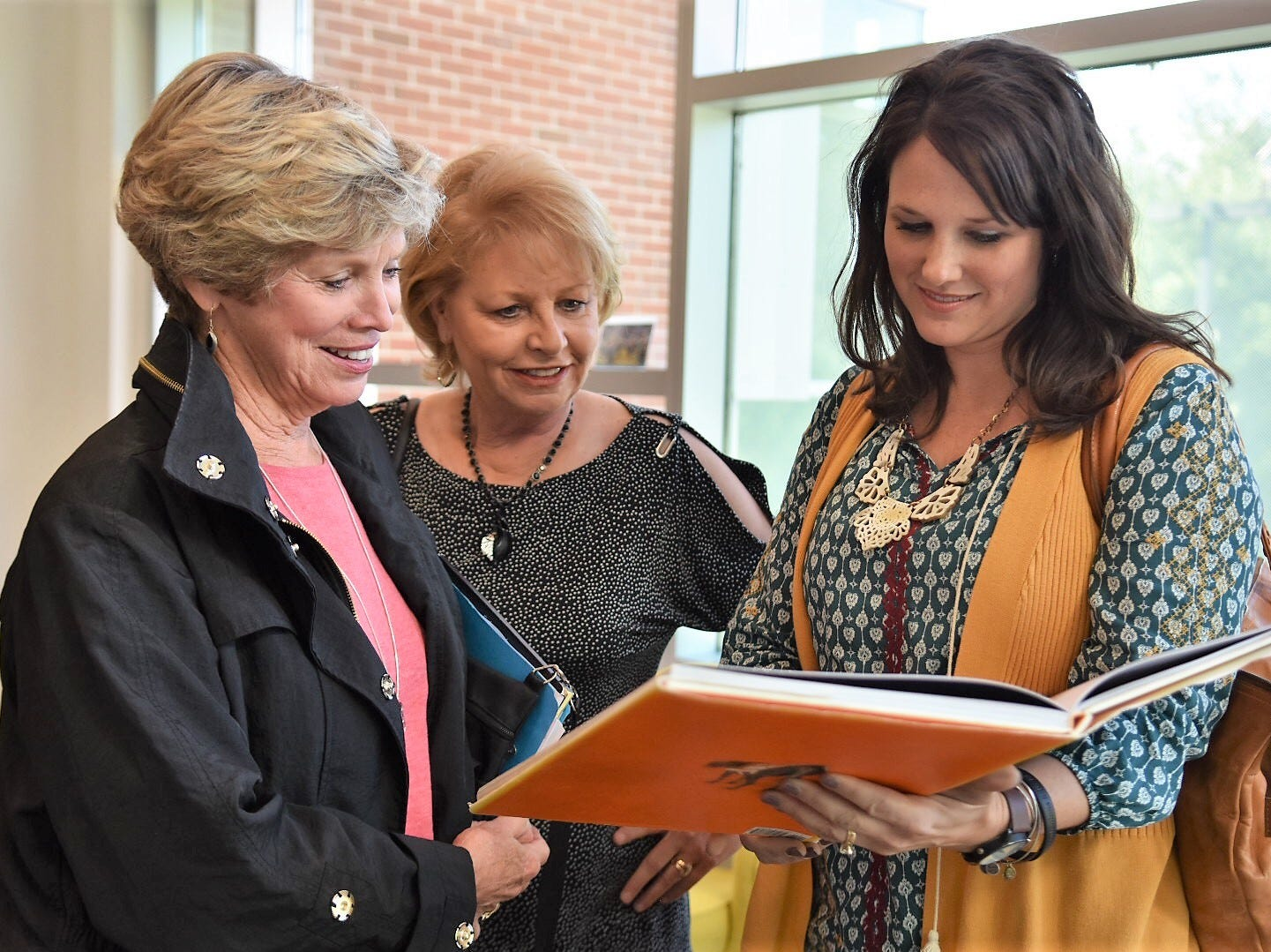 Former UT majorettes Judy Barton Cox, Kathy McCarrell Smith and Carrie DeLozier Creswell look through a book on the history of the Pride of the Southland Band on Wednesday, Oct. 24.