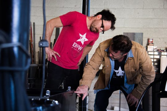 Derek White (right) instructs Ryan Engelhardt, who was working on a fountain at Bird on the Wire Studios on Wednesday.