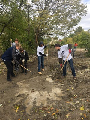 From left, Brighton High School students Charlie Sharp, Parker Tuczak, Patrick Davis, John Louria, and Branden Mayday clear backyards at the tiny homes in Detroit as part of Senior Serve 2018.