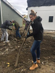 Alexa Bowles, Brighton High School student, removes unnecessary wood and trash from the backyards of tiny homes in Detroit so sod can be laid during Senior Serve 2018.