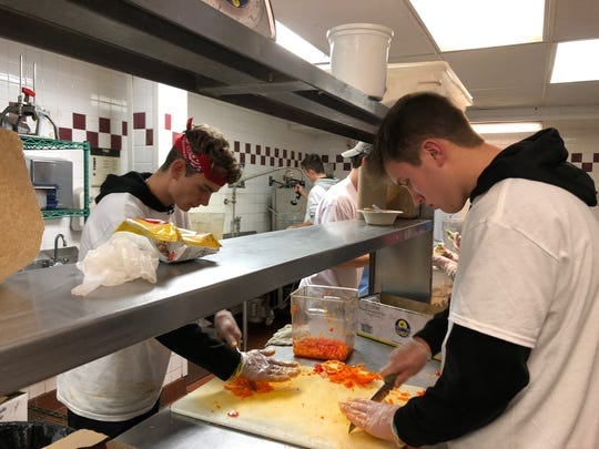 Dylan Smokevitz, left, and Mitchel Brown, Brighton High School students chopping food at the Cass Community soup kitchen in Detroit as part of Senior Serve 2018.