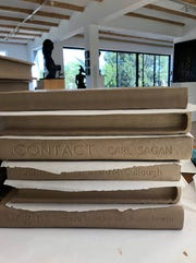 Lauren Caffrey created the lettering on the books in the statue, according to sculptors Colin and Kristine Poole.