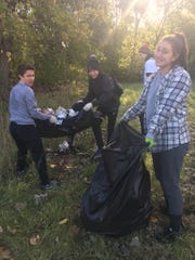 Brighton High School students Nathan Tsiang, Cameron Hurley, and Addison Carriere clean up garbage around the city of Detroit as part of Senior Serve 2018.