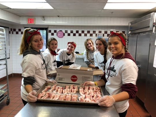 Clockwise from left: Brighton High School students Kennedy Smith, Abbie Bowland, Anna Vergith, Lindsay Hall, Kyla Vida, and Felesity Norris helped prepare meals to feed those in need at the Cass Community Center in Detroit during Senior Serve 2018.