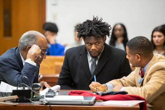 University of Louisville football player Kemari Averett, center, consults with his attorneys, Aubrey Williams, left, and Shaun Wimberly Sr., on right. Averett is charged with assault. Oct. 25, 2018.