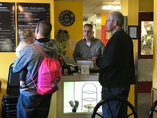 Co-owner Mark Taylor takes orders from customers at Fidler's on the Grand in Lansing.