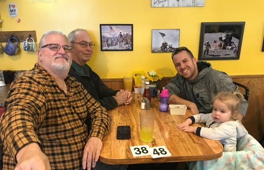 Customers Fred Baer, left, Tim Crawford, Tyler Bergstrom and Amelia Bergstrom wait for their food at Fidler's on the Grand in Lansing.