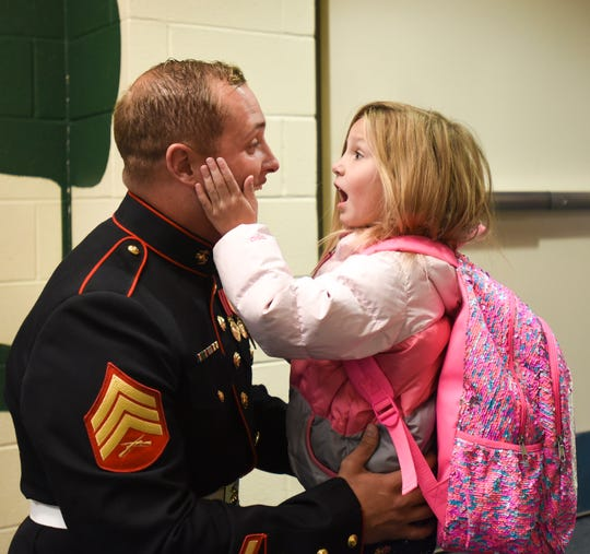 Tears fall from Marine Sgt. Camron Spiece's eyes, as 4-year-old daughter Graycen cups his face on Thursday, Oct. 25, 2018, at Oakview South Elementary School in St. Johns. Sgt. Spiece was discharged Wednesday, after spending about a year recovering from a traumatic brain injury caused when a rocket blew up in his face during combat training in North Carolina.