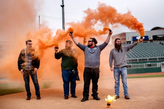 From left, soccer fans Westen Shelton, Eric Gibbs, Rich Scheneck and Alex Hirschman light orange smoke bombs during the announcement of the new professional soccer team Lansing Ignite on Thursday, Oct. 25, 2018, at Cooley Law School Stadium in Lansing.