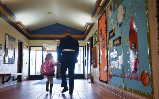 Marine Sgt. Camron Spiece heads toward the doors of Oakview South Elementary School in St. Johns Thursday afternoon, Oct. 25, 2018, with his daughter Graycen, 4, after surprising her at school upon his return home from the Marine Corps.