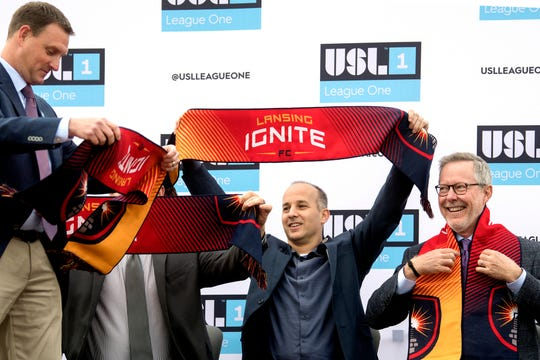 Lansing Ignite Vice President and General Manager Jeremy Sampson left, hands out team scarves to those on stage, including Mayor Andy Schor, center, and Lugnuts/Ignite owner Tom Dickson, during the announcement of the new professional soccer team on Thursday, Oct. 25, 2018, at Cooley Law School Stadium in Lansing.