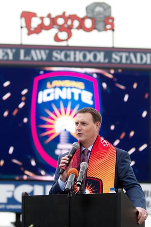 Lansing Ignite vice president and general manager Jeremy Sampson address the crowd on stage while donning a Lansing Ignite scarf during Thursday's announcement ceremony at Cooley Law School Stadium in Lansing.