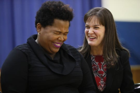Erica Stephens laughs with Tennessee Education Commissioner Candice McQueen as Stephens is announced as the winner of the Milken Educator Award during an assembly at John P. Freeman Optional School.