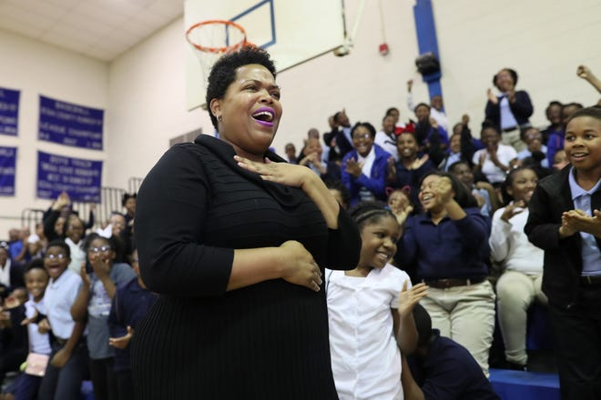 Erica Stephens is surprised by the announcement that she has won the Milken Educator Award, as her students cheer her on in the background, during an assembly Thursday at John P. Freeman Optional School. The national accolade made Stephens one of 40 recipients nationwide, recognizing her for her work with a $25,000 award.