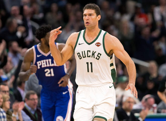 Bucks center Brook Lopez signals as he runs down the court after hitting 1 of his 5 three-pointers on the night against the 76ers on Wednesday.