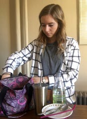 University of Wisconsin-Stevens Point senior Jenessa Gilarski loads her backpack for the day with silverware (to avoid needing plastic silverware), a water bottle, a coffee travel mug, grandmother's plate for her lunch and both stainless steel and silicone straws.
